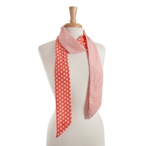 """Reversible coral skinny scarf with white polka dots on one side and white stripes on the other. Can also be worn as a headband. 100% polyester.  Approx. 68"""" x 2.5"""""""