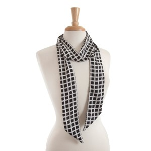 Lightweight black skinny scarf with a white checker pattern that can also be worn as a headband. 100% polyester.