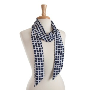 "Lightweight navy blue skinny scarf with a white checker pattern that can also be worn as a headband. 100% polyester. Approx. 68"" x 2.5"""