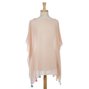 Blush pink short sleeve poncho with multicolored pom poms on the bottom hem. 30% cotton and 70% polyester. One size fits most.