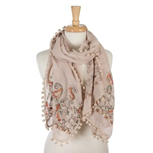 """Beige, lightweight scarf with floral embroidery and pom poms on the outer trim. 65% polyester and 35% viscose. Measures 26"""" x 70"""" in size."""