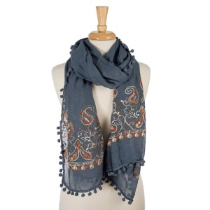"""Denim blue, lightweight scarf with floral embroidery and pom poms on the outer trim. 65% polyester and 35% viscose. Measures 26"""" x 70"""" in size."""