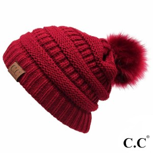 Cable knit, original C.C beanie with a self color faux fur pom pom, in red. 100% acrylic.