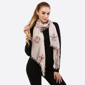 Lightweight embroidered scarf with pom pom detail.   - 100% Acrylic.