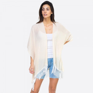 "Solid ivory kimono with lace down the back and fringe detailing. One size fits most 0-14. Measures approximately 37"" x 27"" in size. 65% Polyester, 35% Cotton."