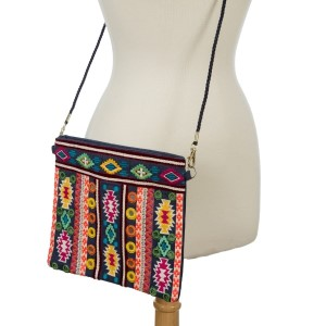 """Navy blue canvas handbag with a multicolored Aztec print on the front, a top zipper, and a crossbody strap. Measures 10"""" x 8.5"""" in size."""