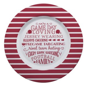 "Gameday melamine plate in crimson and white, that reads ""We're a game day loving, jersey wearing, always cheering, pregame tailgating, rival team hating, every game watching, football family. Measures 14"" in diameter and is dishwasher safe."