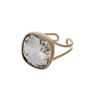 Gold tone adjustable ring with a faceted clear stone.