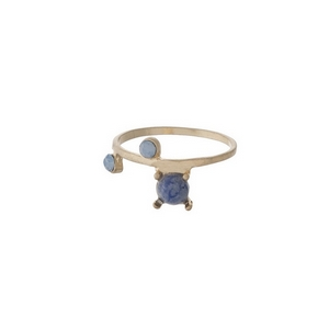 Gold tone ring with a blue stone, accented by rhinestones. Approximately a size 7.