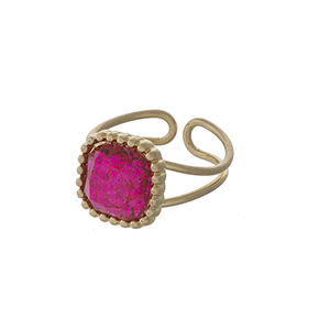 Gold tone adjustable ring with a pink glitter stone focal.