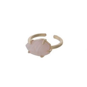 Adjustable, gold tone ring with a pale pink stone.