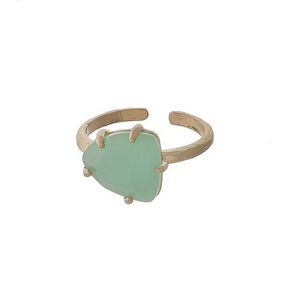 Adjustable, gold tone ring with a mint green stone.