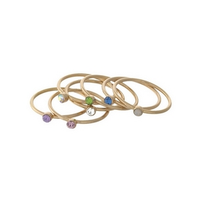 Dainty gold tone, six piece ring set with multicolored rhinestones on each. All rings approximately a size 7 and cannot be adjusted.