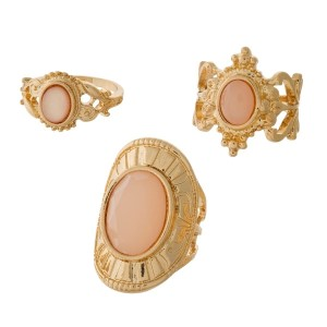 Three piece gold tone ring set with blush pink stones. All three rings are approximately a size 7 and are not adjustable.
