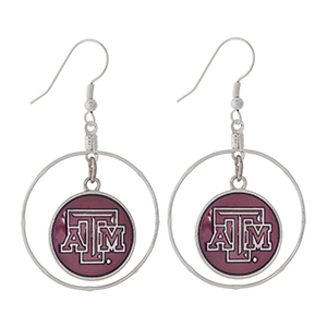 "Silver tone fishhook earrings displaying a ring with a dangling officially licensed maroon Texas A&M University charm. Charm approximately 1 1/2"" in length. Overall length 2 1/8""."