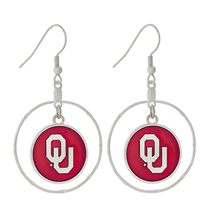 "Silver tone fishhook earrings displaying a ring with a dangling officially licensed red University of Oklahoma charm. Approximately 1 1/2"" in length."