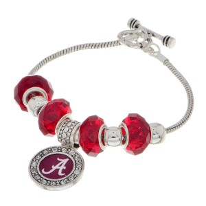 "Officially licensed 7"" Silver tone toggle closure charm bracelet featuring an Alabama logo charm accented by red and silver tone sliding charms."