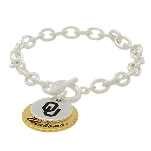 "Silver tone officially licensed collegiate toggle bracelet featuring two mixed metal disk stamped ""OU"" and ""Oklahoma"". Approximately 7"" in length."