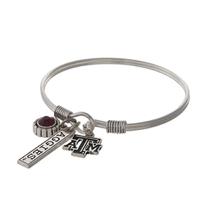 Officially licensed Texas A&M University silver tone bracelet with a maroon rhinestone, logo, and Aggies stamped bar charm.