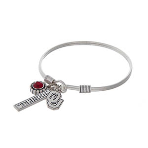 Officially licensed silver tone hook bracelet featuring a red rhinestone, Oklahoma logo, and a bar stamped with Sooners.